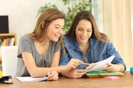 Zwei Studenten machen Hausaufgaben zusammen und helfen einander sitzen in einem Tisch zu Hause mit einem heimischen Hintergrund