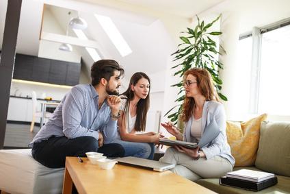 Weibliche Immobilienmakler bieten Hausbesitz und Lebensversicherung für junge Paare.