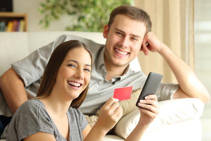 Paar von Online-Käufer kaufen mit Kreditkarte und Smartphone posieren und Blick auf Kamera