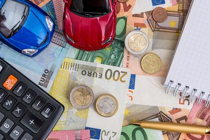 Zwei Autos mit Euro-Rechnungen, Notizblock und Stift