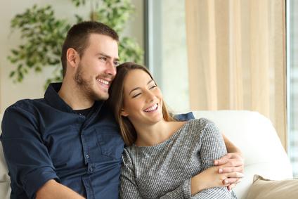 Zufriedene paar Hausbesitzer, die auf einem Sofa sitzen und durch das Fenster des Wohnzimmers zu Hause schauen