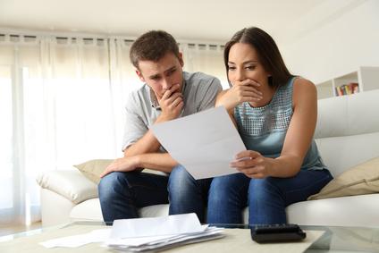 Besorgtes Paar liest einen Brief, der auf einer Couch im Wohnzimmer zu Hause sitzt
