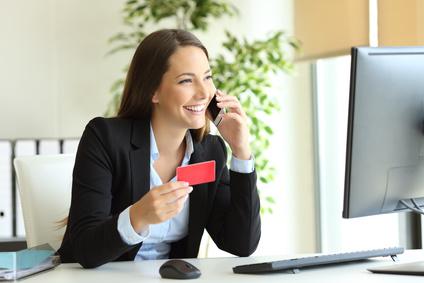 Gluekliche Geschaeftsfrau arbeitet Kauf online mit Kreditkarte und ruft Kundenservice im Buero
