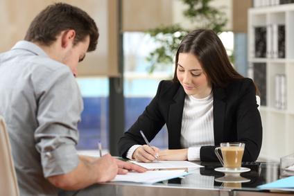 Geschäftsleute unterzeichnen Verträge zusammen nach einem Deal in einem Desktop im Büro